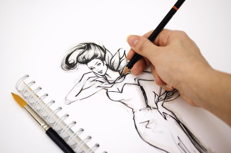 Close-up of an illustrator hand drawing a fashion sketch.  royalty free stock images