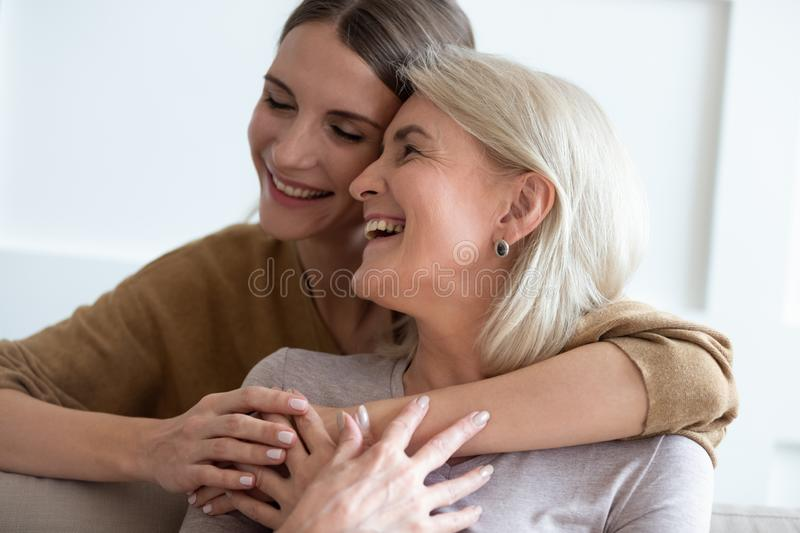 Closeup adult daughter hugs elderly mother enjoy tender moment. Close up image beautiful faces of happy european women different generations indoors, adult 30s stock images