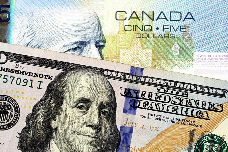 A blue Canadian five dollar bill with an American one hundred dollar bill. A close up image of a blue Canadian five dollar bill with an American one hundred stock photo