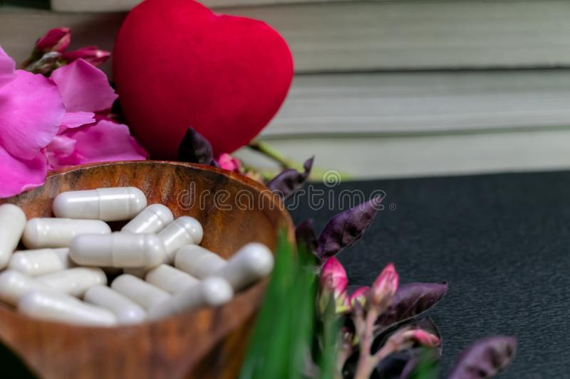 Close up image of books behind the herbal medicine capsules in a wood spoon with red heart, pink flowers and green leaf on dark royalty free stock photos