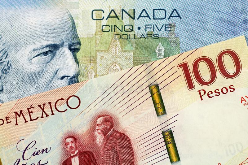 A Canadian 5 Dollar bill with a Mexican 100 peso note. A close up image of a 5 Canadian dollar bill with a 100 Mexican Peso Bank note royalty free stock image