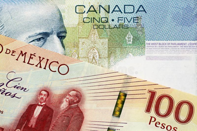 A Canadian 5 Dollar bill with a Mexican 100 peso note. A close up image of a 5 Canadian dollar bill with a 100 Mexican Peso Bank note stock photo