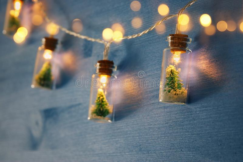 Photo of Christmas tree in the masson jar garland lights over wooden blue background. Close up image of Christmas tree in the masson jar garland light over stock image
