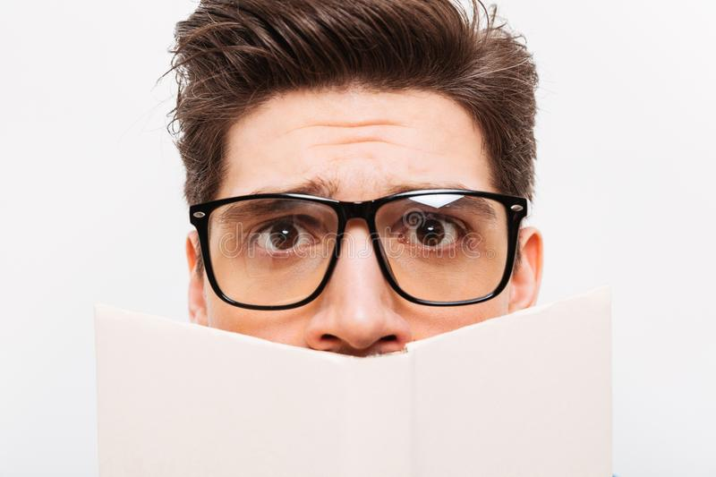 Close-up image of Confused nerd in eyeglasses hiding behind book stock photos