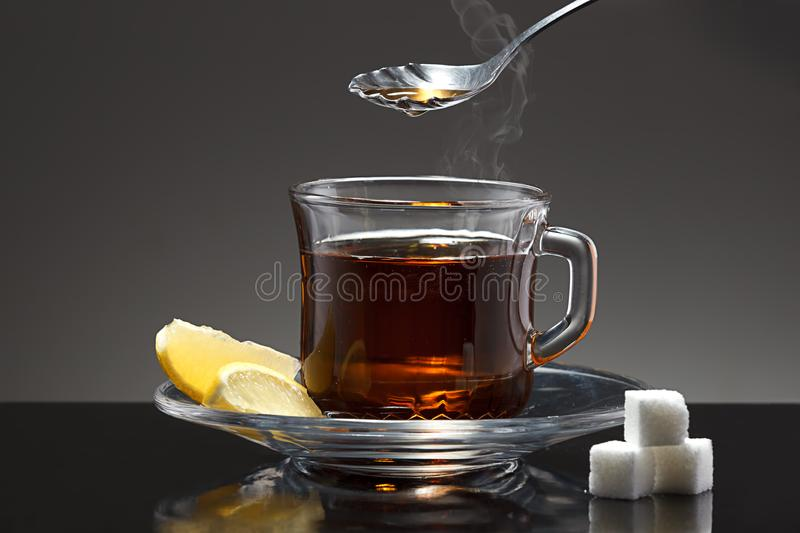 Spoon above cup of hot tea. royalty free stock image