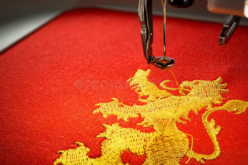 Close up image of embroidery machine and embroider gold lion on red fabric. Copy space on the left side royalty free stock photos