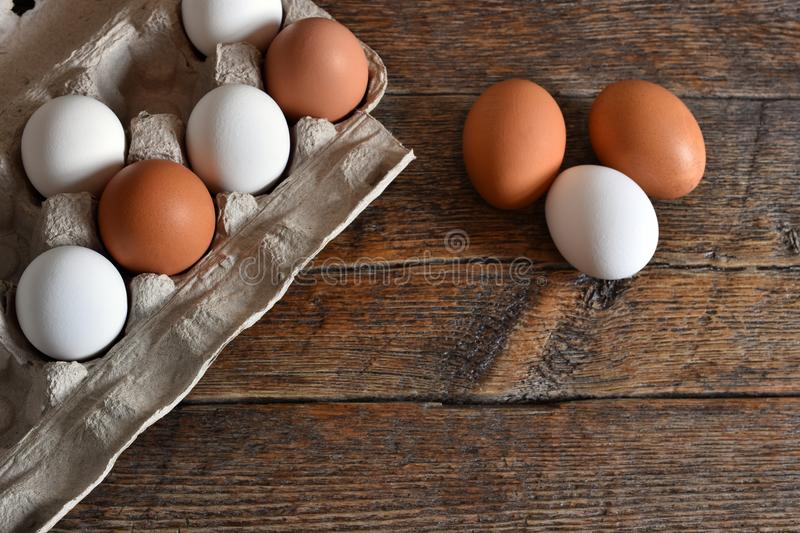 Farm Fresh Organic Eggs. A close up image of farm fresh organic eggs in a paper egg carton on a rustic wooden table royalty free stock images