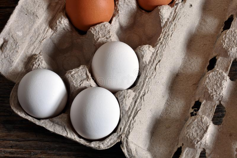 Farm Fresh Organic Eggs. A close up image of farm fresh organic eggs in a paper egg carton on a rustic wooden table royalty free stock image