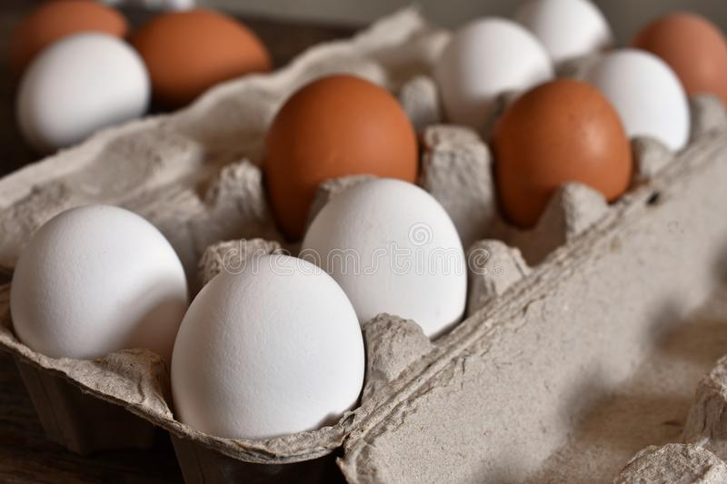 Farm Fresh Organic Eggs. A close up image of farm fresh organic eggs in a paper egg carton on a rustic wooden table stock photos