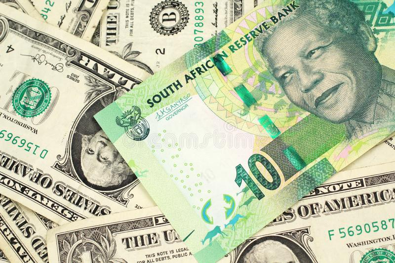 A ten South African rand bank note on a bed of American dollar bills. A close up image of a green ten rand bank note from South Africa in macro on a bed of royalty free stock photos