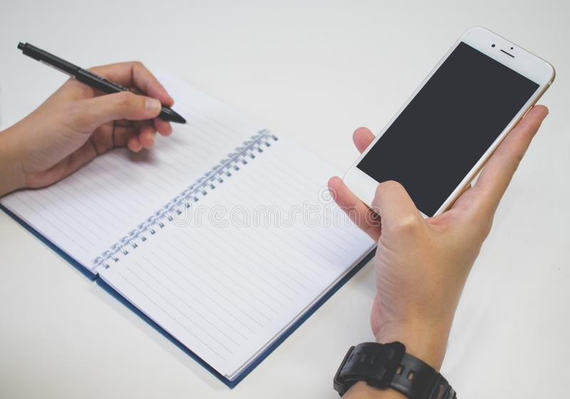 Close up image. A hands with pen writing on notebook and using smartphone at the same time. stock image