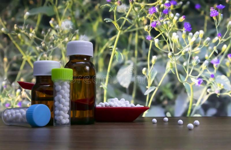 Close-up image of homeopathic pills in red spoon and bottle of liquid and globules substance with spread white sugar balls on wood royalty free stock photos