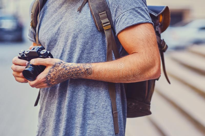 A man holds a compact film camera with tattooed arms. Close up image of a man holds a compact film camera with tattooed arms royalty free stock image
