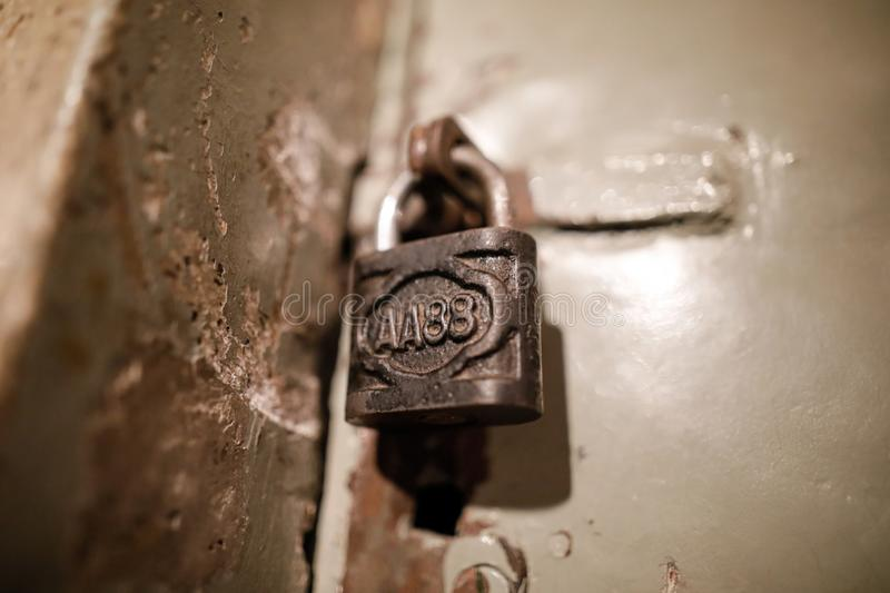 Close up image with a metallic old and rust lock on the door of a communist Romania Securitate prison cell stock photos