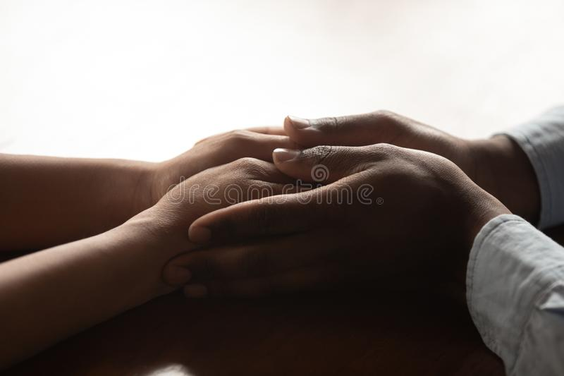 Close up millennial african amarican loving man holding wifes hands. stock photography