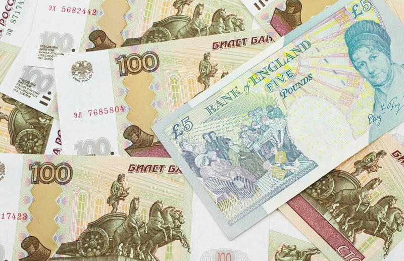A UK five pound note on a background of Russian one hundred ruble bills royalty free stock photo