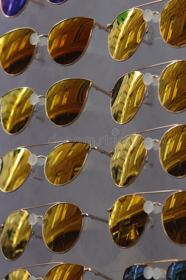 Close up of multiple yellow sunglasses with reflections of historical buildings of Galata, Istanbul. Close up image of multiple cool yellow sunglasses with stock photos