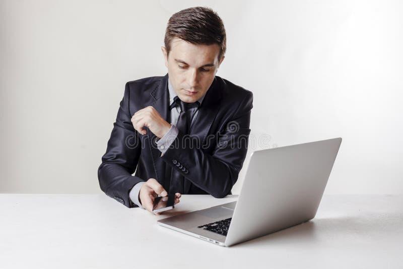 Close up image of multitasking business man using a laptop and mobile phone. Close up image of multitasking business man using a laptop and cell phone stock photography