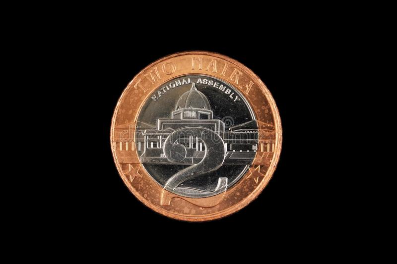 Nigerian Two Naira Coin Isolated On A Black Background. A close up image of a Nigerian bimettalic two Naira coin isolated on a black background royalty free stock photos