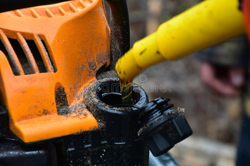 Chainsaw and Mix Oil. A close up image of an old dirty chainsaw with mix oil being added royalty free stock images