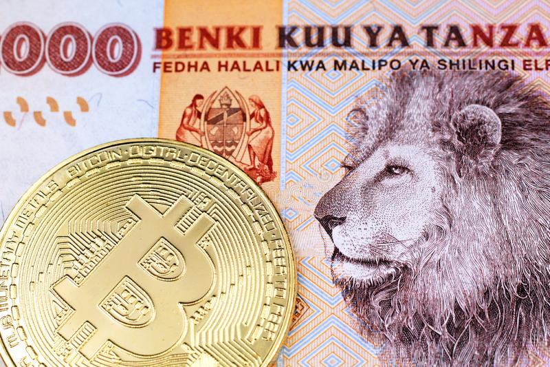 A colorful 2000 Tanzanian shilling bank note wih a gold physical bitcoin in macro. A close up image of an orange, Tanzanian two thousand shilling note with a royalty free stock photos
