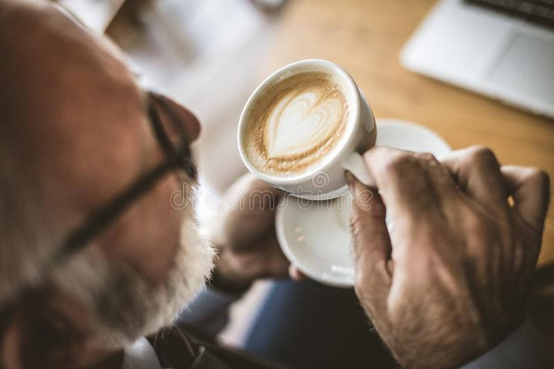 Close up image of senior businessman drinking coffee. royalty free stock images