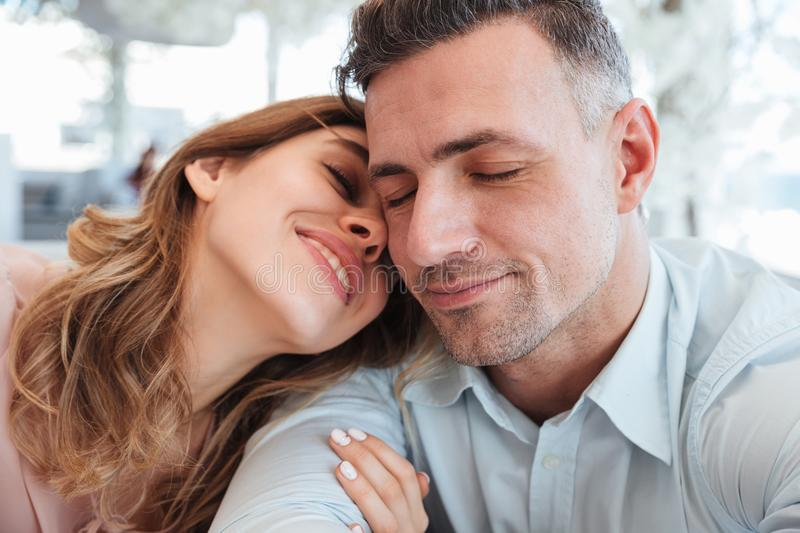 Close up image of Sensual lovely couple sitting togther. With closed eyes by the table in cafe stock images