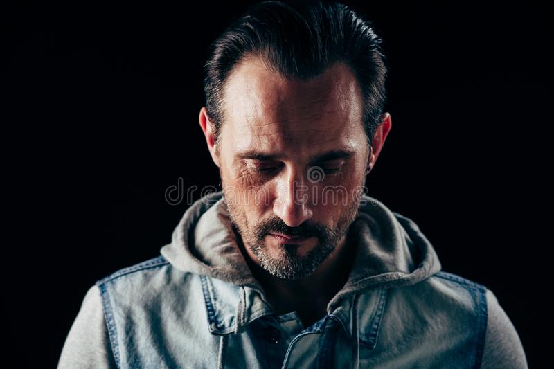 Serious strong man. Close up image of man with down look. Real man concept stock photography