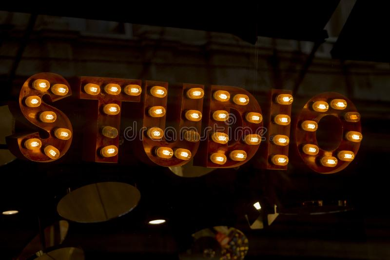 Close up image of a sign with the text `Studio` written with retro lamps in sans serif typography royalty free stock image