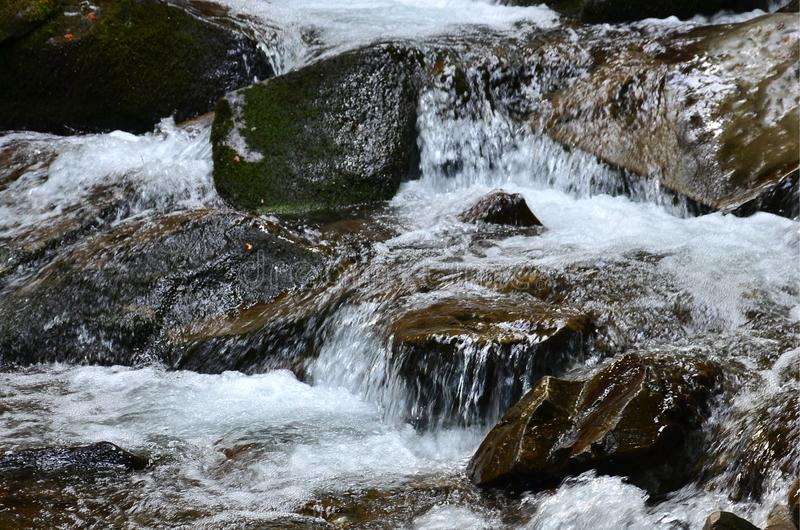 Close-up image of a small wild waterfall in the form of short streams of water between mountain stones royalty free stock photos