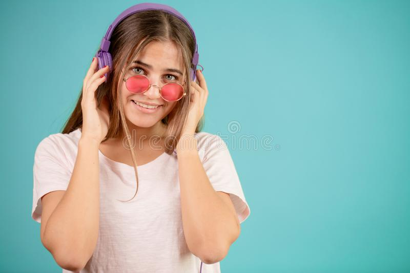 Close up image of smiling female DJ in blue headphones and rose sunglasses stock images