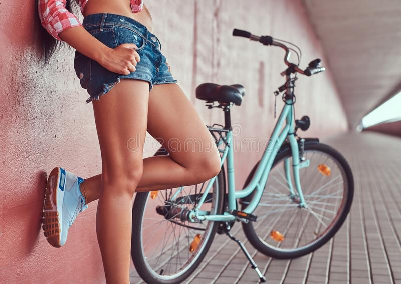 Close-up image of smooth slim female legs in blue sneakers, leaning against a pink wall, near blue city bike stock photography