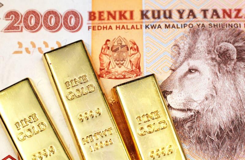 An orange two thousand Tanzanian shilling note with three small gold bars. A close up image of three small gold ingots with an orange two thousand Tanzanian bank royalty free stock photo