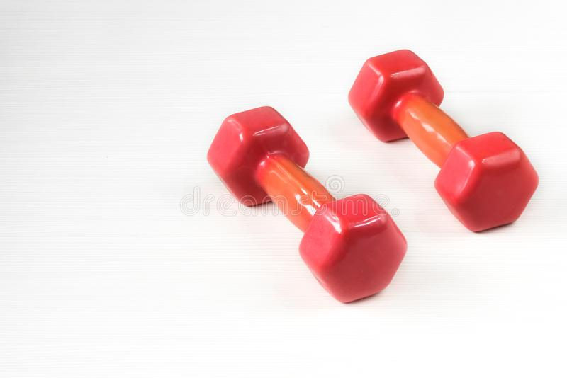 Close-up image of two pink dumbbells isolated on white wooden background stock images