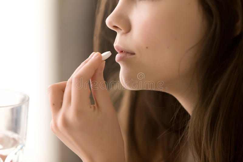 Close up image of woman drinking round white pill stock photos