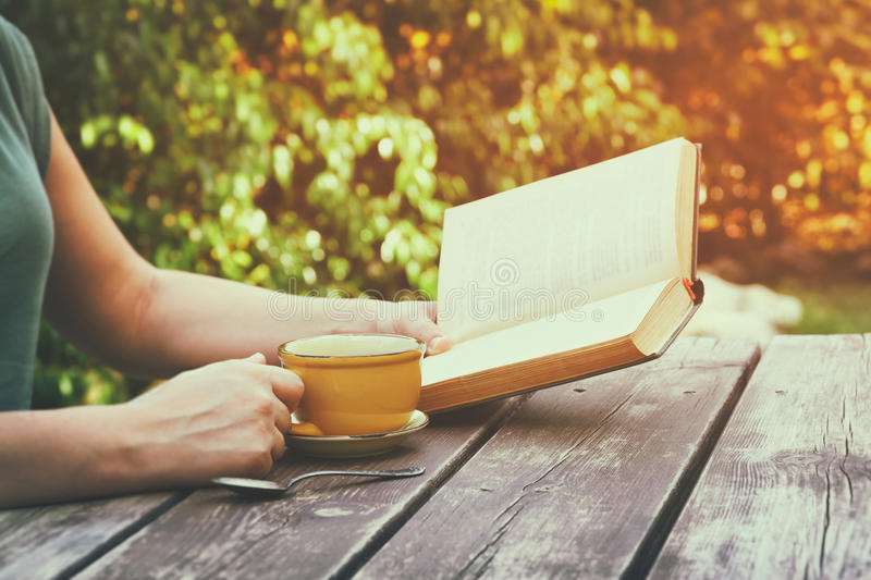 Close up image of woman reading book outdoors, next to wooden table and coffe cup at afternoon. filtered image. filtered image stock photo
