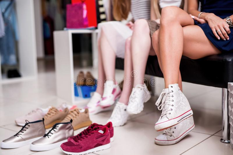 Close-up image of women sitting with legs crossed trying on new sneakers in shopping center.  stock images