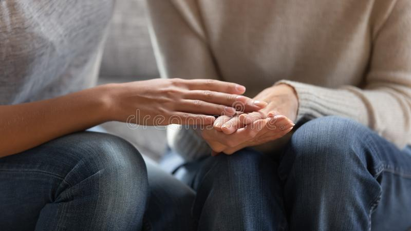 Close up image adult daughter touches hands of aged mother stock photography