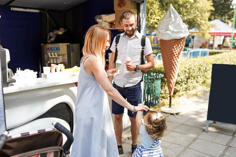 Close-up image of a young happy family spending their weekend in the park and eating ice-cream royalty free stock photo