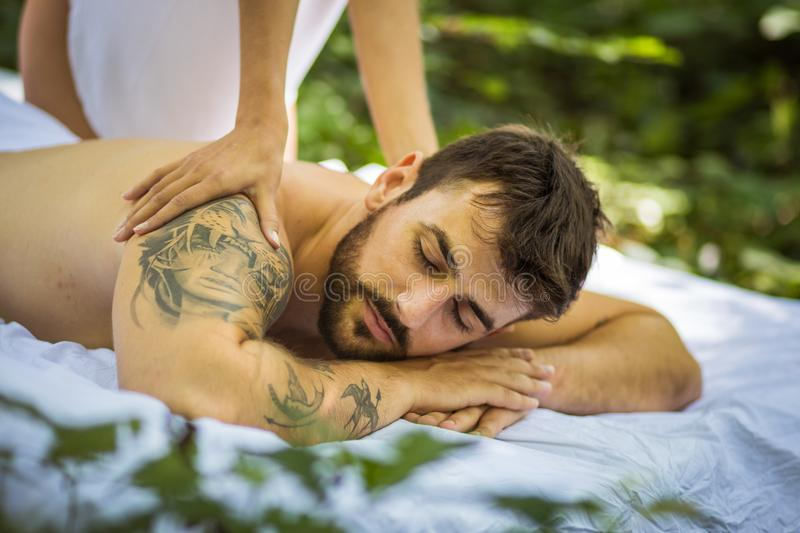 Close up image of young men at massage treatment. Nature stock photo