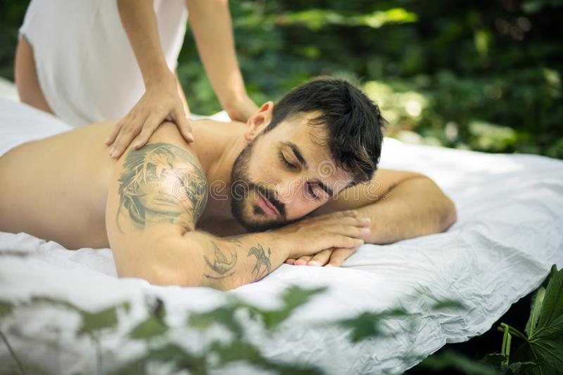 Close up image of young men at massage treatment. Close up image of young men at massage treatment by his girlfriend royalty free stock images