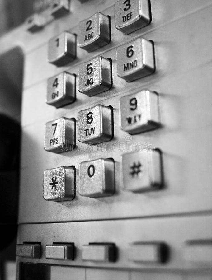 Telephone from a telephone booth in black and white. Close up images of a telephone from a telephone booth from the 1990`s. Space for copy royalty free stock image