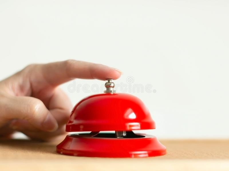 Close-up of index finger pressing the bell button of red vintage style handbell on wooden table stock photography