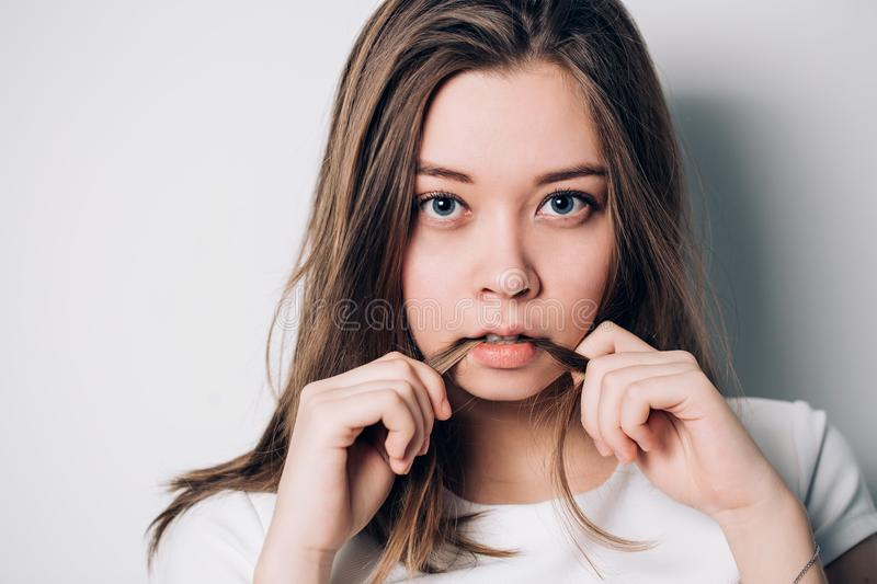 Close up indoor fashion lifestyle portrait of cool pretty young brunette girl, making crazy funny grimace, royalty free stock photography