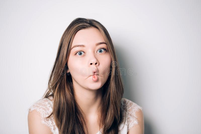 Close up indoor fashion lifestyle portrait of pretty young brunette girl, cute face, making crazy funny grimace. royalty free stock photos