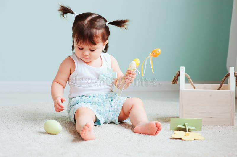 Indoor portrait of cute happy baby girl playing with easter decorations royalty free stock images