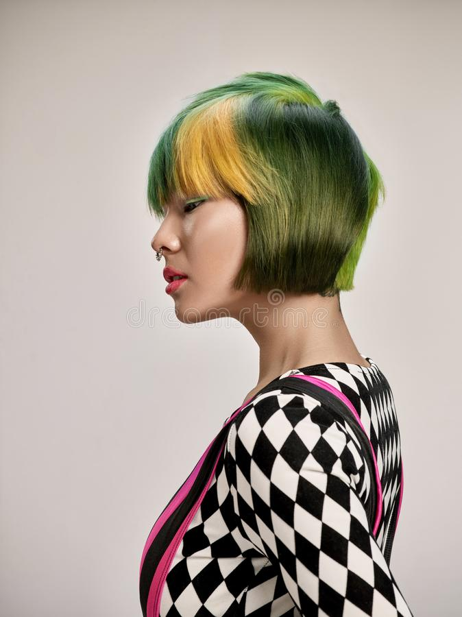 Close-up indoor portrait of lovely girl with colorful hair. Studio shot of graceful young woman with short haircut royalty free stock images