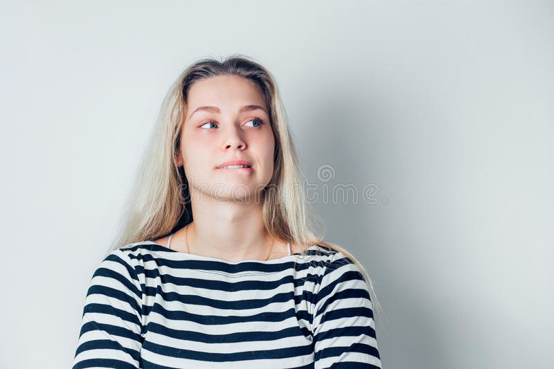 Close up indoor portrait of young dissatisfied woman biting lower lips on white background with copy space stock photography