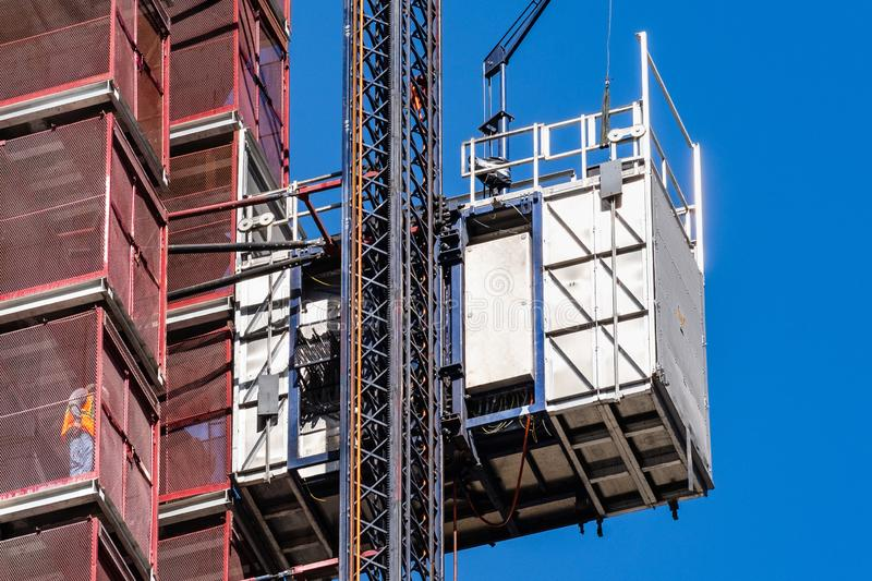 Close up of industrial hoist used to lift workers and materials at a construction site stock photography