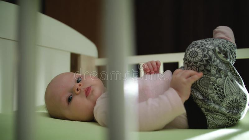 Close up of Infant Baby Laying in Crib Legs Up Motion. Close up video of infant baby laying in Crib holding legs up through wooden sticks motion evening stock photos